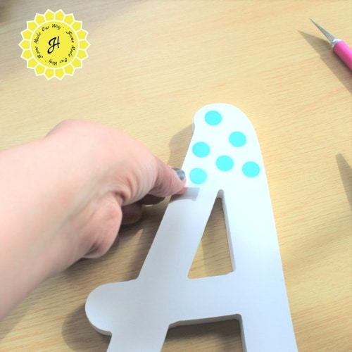 applying washi tape polka dots to wooden letter A