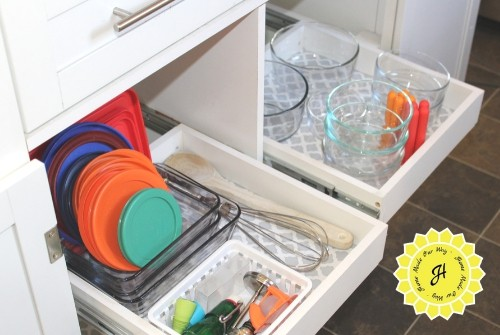 kitchen island with pull out drawers holding glassware, lids, and utensils