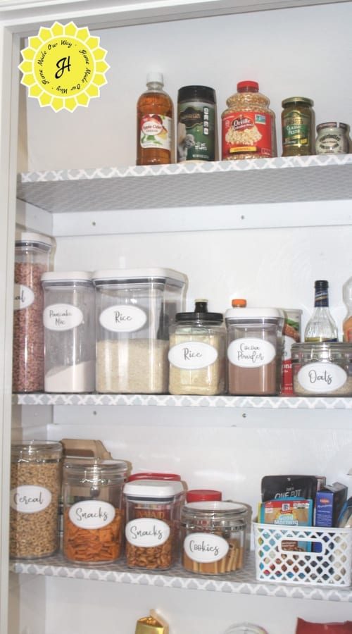 pantry with shelves and labeled food canisters