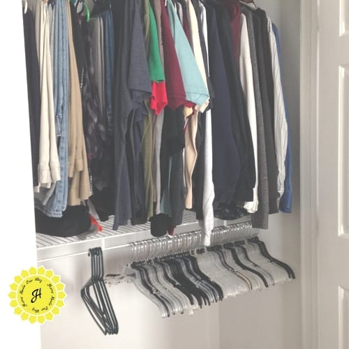 closet with two shelves: top shelf is full of tops and the other is empty except for hangers