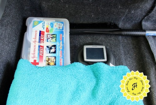contents of car storage: first aid kit, ice scraper, gps, and blankets