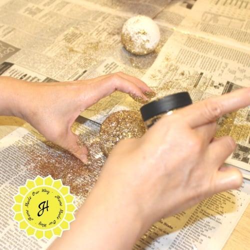 adding glitter onto golden snitches styrofoam ball