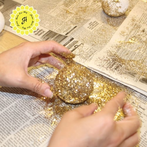covering golden snitches styrofoam ball with golden glitter