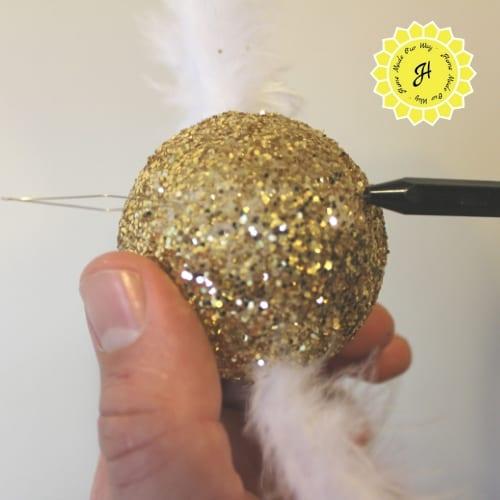inserting bobbin into styrofoam ball
