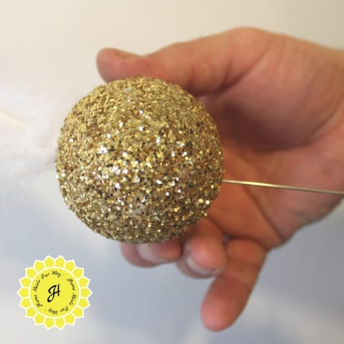 inserting bodkin into styrofoam ball