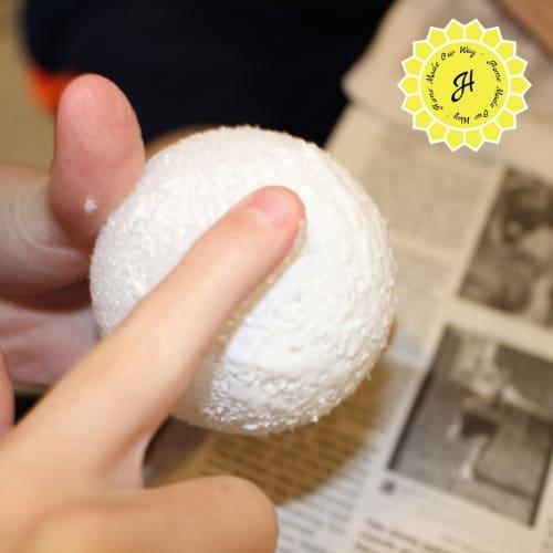 spreading glue on styrofoam ball