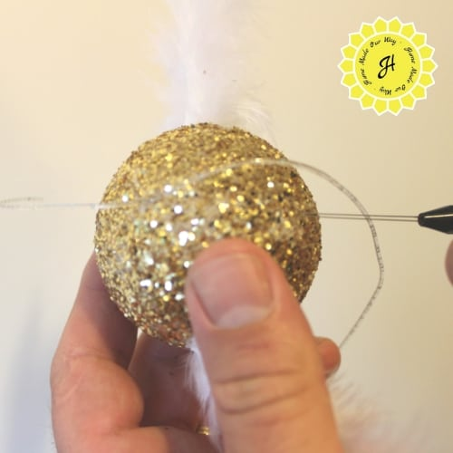 pulling threading cord through puncture holes in styrofoam ball with bobbin